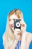 Nette junge Frau in Sommer gestreiftem Kleid benutzt Retro- Kamera auf blauem Hintergrund im Studio Stockfotografie