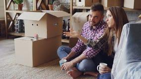 Nette junge Frau spricht mit ihrem Ehemann über ihr neues Haus, das auf Boden während der Verlegung sitzt Glückliche Leute stock footage