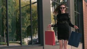 Nette junge Frau springt in die Aufregung, die ihre Einkaufstaschen hält stock video