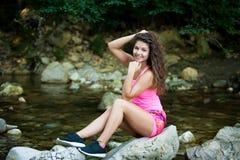 Nette junge Frau steht auf einem Felsen im Flussbett auf Spätsommer achtern still Lizenzfreie Stockfotografie