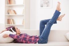 Nette junge Frau steht zu Hause still stockbilder