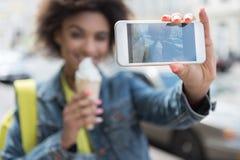 Nette junge Frau tut ihr Bild unter Verwendung des Handys Stockfotografie