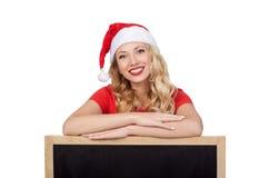 Nette junge Frau in versteckendem Gesicht Weihnachtsmann-Hutes hinter leerem weißem Brett Stockbilder