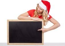 Nette junge Frau in versteckendem Gesicht Weihnachtsmann-Hutes hinter leerem weißem Brett Stockfotografie