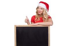 Nette junge Frau in versteckendem Gesicht Weihnachtsmann-Hutes hinter leerem weißem Brett Lizenzfreie Stockfotos
