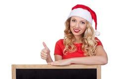 Nette junge Frau in versteckendem Gesicht Weihnachtsmann-Hutes hinter leerem weißem Brett Lizenzfreie Stockfotografie