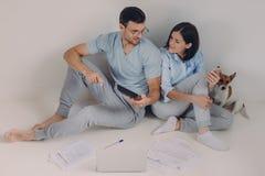 Nette junge Frau verwendet das Ein Bankkonto haben von App an ihrem Handy, sein Ehemann zeigt Zahlen auf dem Taschenrechner, umge lizenzfreie stockbilder