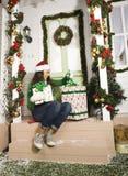 Nette junge Frau an verziertem Haus mit Geschenken Lizenzfreies Stockbild