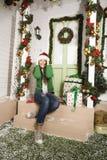 Nette junge Frau an verziertem Haus mit Geschenken Stockbild