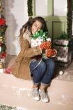 Nette junge Frau an verziertem Haus mit Geschenken Lizenzfreie Stockfotos