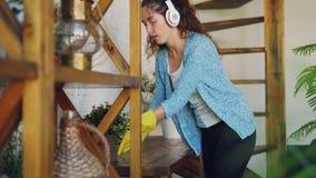 Nette junge Frau wäscht die Tabelle zu Hause und hört Musik mit Kopfhörern, dem Gesang und dem Tanzen Mädchen ist stock video