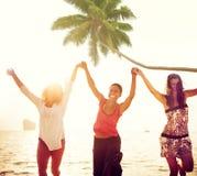 Nette junge Frauen, die durch den Strand feiern Lizenzfreies Stockfoto