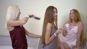 Nette junge Frauen mit dem schönen Haar in den Pyjamas treten morgens zusammen beim Raumklatschen-Gesprächsverkratzen zusammen stock video footage