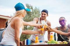 Nette junge Freunde, die Bier trinken und draußen feiern Stockfoto