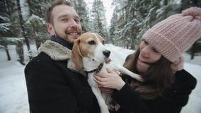 Nette junge Hippie-Paare, die Spaß im Winterpark mit ihrem Hund an einem hellen Tag und an einem Lächeln haben Mann- und Frauensp stock footage