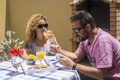 Nette junge kaukasische Paare frühstücken zusammen im Garten zu Hause unter der Sonne schöner Tag des Sommers oder des Frühlinges lizenzfreies stockfoto