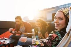 Nette junge Leute, die auf Dach mit Lebensmittel sich entspannen lizenzfreie stockfotos