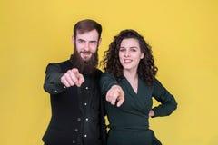 Nette junge Leute, die Finger auf Kamera zeigen stockfotos