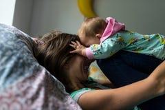 Nette junge Mutter, die mit ihrer Tochter spielt lizenzfreie stockbilder