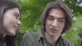 Nette junge Paare des Portr?ts in der zuf?lligen Kleidung, die zusammen Zeit im Park, ein Datum habend verbringt Der Kerl, der un stock video
