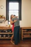 Nette junge Paare, die in der Küche sich umfassen Lizenzfreie Stockfotografie