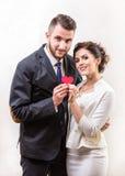 Nette junge Paare, die Papierherz und das Lächeln halten lizenzfreie stockfotos