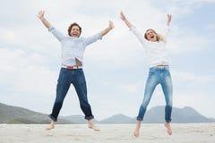 Nette junge Paare, die am Strand springen Lizenzfreies Stockfoto