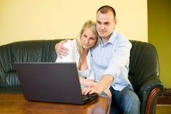 Nette junge Paare mit Laptop zu Hause. Stockfoto