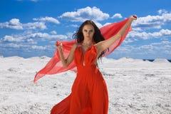 Nette junge reizvolle Frau im roten Kleid auf dem Schnee Stockbild