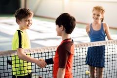 Nette Jungen, die Hände rütteln, bevor Tennis gespielt wird lizenzfreie stockfotos