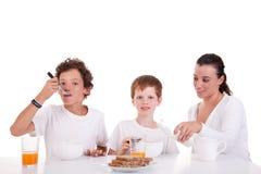 Nette Jungen und Mutter, die Frühstück nimmt stockbilder