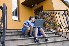 Nette Jungenuntersuchung über Computer stockfotografie