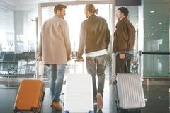 Nette Kameraden, die in Halle mit Koffern umziehen stockfoto