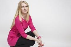 Nette kaukasische blonde Frau im rosa Kleid, das gegen Weiß aufwirft Lizenzfreies Stockfoto
