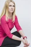 Nette kaukasische blonde Frau im rosa Kleid, das gegen Weiß aufwirft Stockfotografie