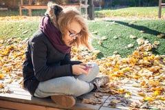 Nette kaukasische blonde Jugendliche mit Mobiltelefon Stockbild