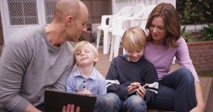 Nette kaukasische Familie, die Handgeräte sitzt und betrachtet Stockfoto