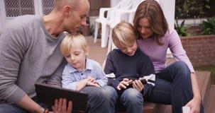 Nette kaukasische Familie, die Handgeräte sitzt und betrachtet Stockfotografie