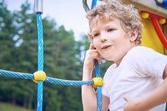 Nette kaukasische Farben des kleinen Jungen mit Kreide auf einer Tafel Stockfoto