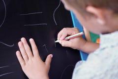 Nette kaukasische Farben des kleinen Jungen mit Kreide auf einer Tafel Stockbilder