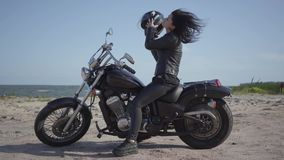 Nette kaukasische Frau in einer schwarzen Lederjacke und in einem Sturzhelm, die auf Motorrad sitzen Mädchen entfernt den Sturzhe stock footage
