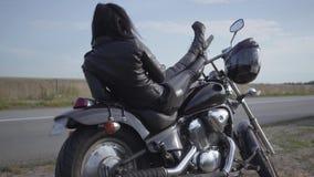 Nette kaukasische Frau in einer schwarzen Lederjacke und in Hosen, die auf einem klassischen Motorrad liegen Hobby, reisend und a stock video