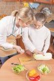 Nette kaukasische Mutter und jugendliche Tochter, die Gemüse vorbereitet Stockfotos