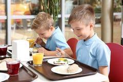 Nette Kinder bei Tisch mit gesunder Nahrung in der Schule stockfotografie