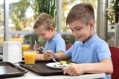 Nette Kinder bei Tisch mit gesunder Nahrung in der Schule lizenzfreies stockbild