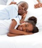 Nette Kinder, die auf Bett ihrer Muttergesellschafts liegen