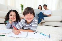 Nette Kinder, die das Lügen auf dem Fußboden zeichnen Lizenzfreie Stockbilder