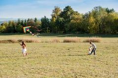 Nette Kinder, die einen Drachen fliegen Lizenzfreie Stockfotos