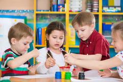 Nette Kinder, die mit bunten Farben am Kindergarten zeichnen stockbild