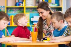 Nette Kinder, die mit Lehrer an der Vorschulklasse zeichnen Lizenzfreies Stockbild